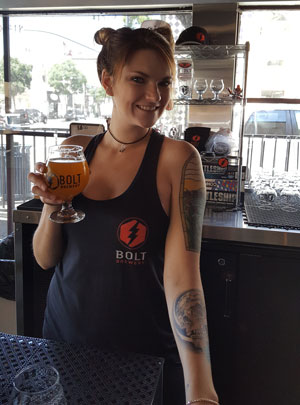 Woman holding a glass of Bolt Beer